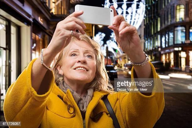 Senior woman takes Selfie in city at night.