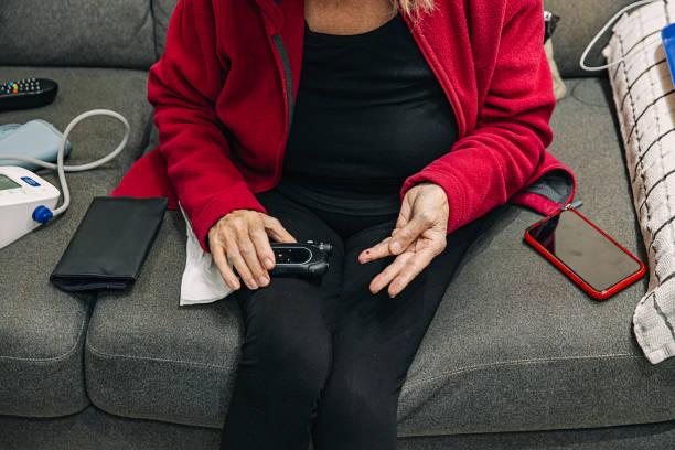 Senior woman taking blood sugar reading