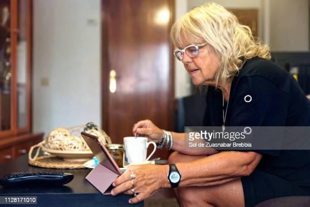 Senior woman taking breakfast and using her digital tablet