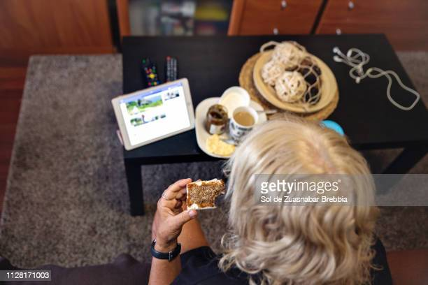 Senior woman taking breakfast in the living room and using her digital tablet