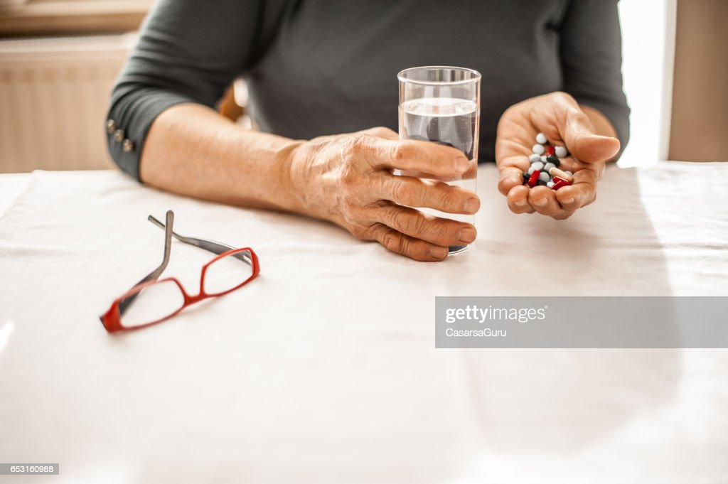 Senior kvinna tar daglig medicin : Bildbanksbilder