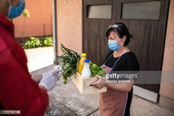 senior woman taking groceries from caring volunteer during covid-19 lockdown - charitable donation stock pictures, royalty-free photos & images