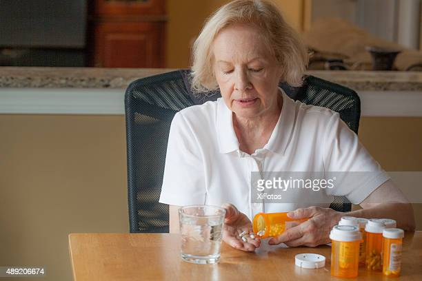 senior woman taking her daily medicine - glas serviesgoed stockfoto's en -beelden