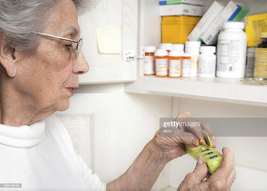 senior woman taking medicine from pill organizer : Stock Photo