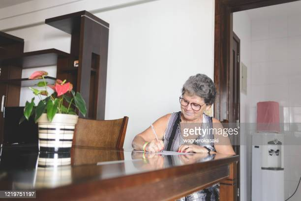 senior woman taking notes or filling forms at home - handwriting stock pictures, royalty-free photos & images