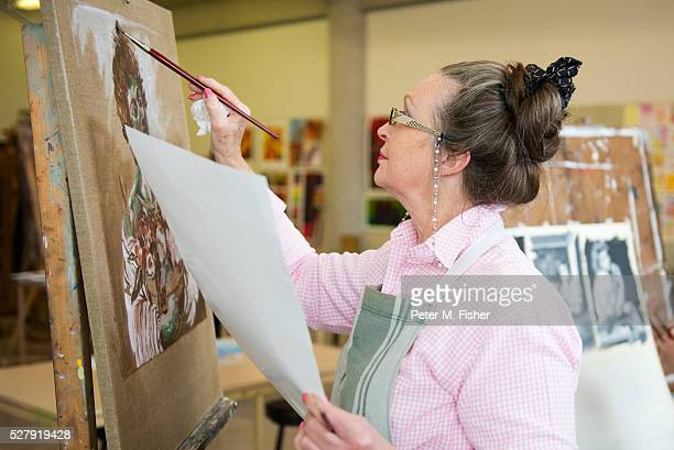 Senior woman taking painting lesson