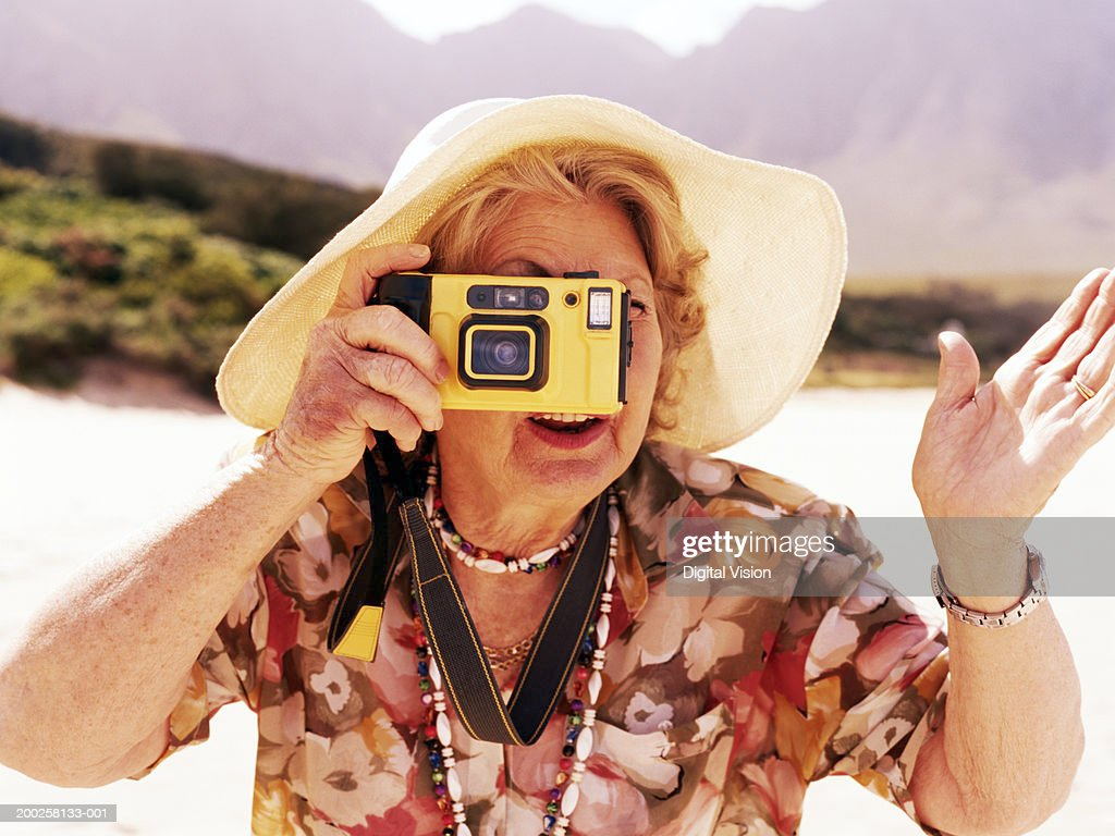 Senior woman taking photograph outdoors : Stock Photo