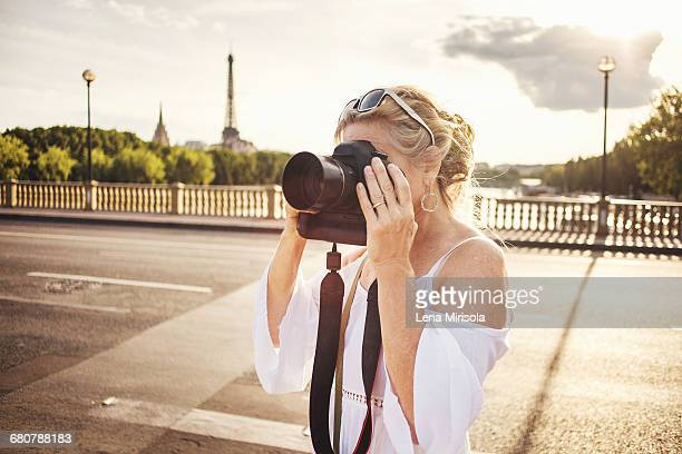Senior woman taking photograph with camera, Paris, France