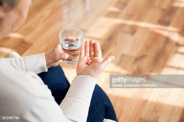 senior woman taking pills - taking a pill stock pictures, royalty-free photos & images