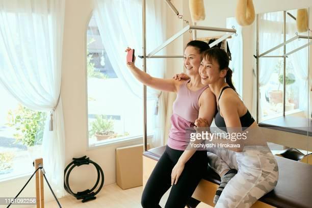 senior woman taking selfie with owner in pilates classroom - スポーツ  ストックフォトと画像