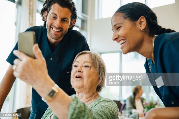 senior woman taking selfie with smiling male and female nurses at retirement home - incidental people stock pictures, royalty-free photos & images