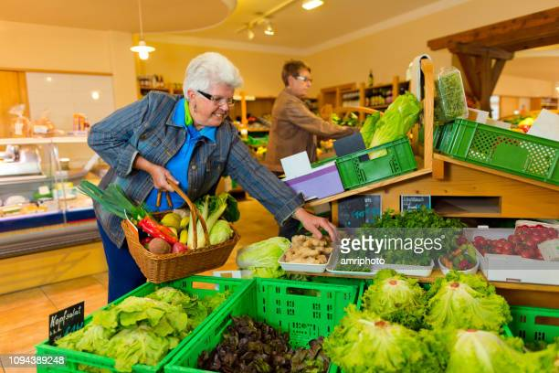 senior woman taking some fresh salad in health food shop - health food shop stock pictures, royalty-free photos & images