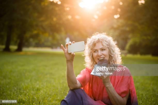 Senior woman taking summer chocolate selfie