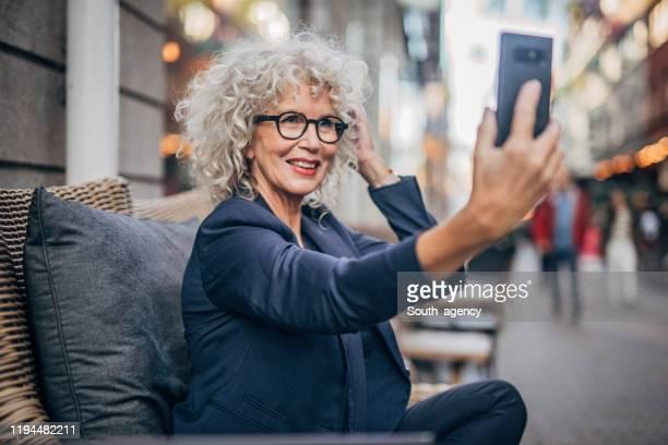 senior vrouw praten een selfie buitenshuis in café - brillen en lenzen stockfoto's en -beelden