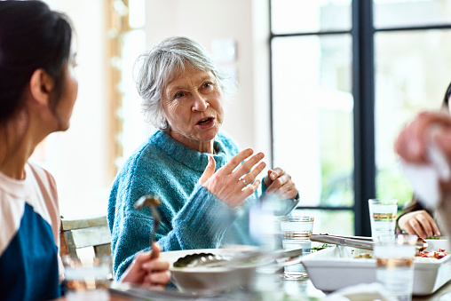 Senior woman talking and gesturing at dinner party - gettyimageskorea