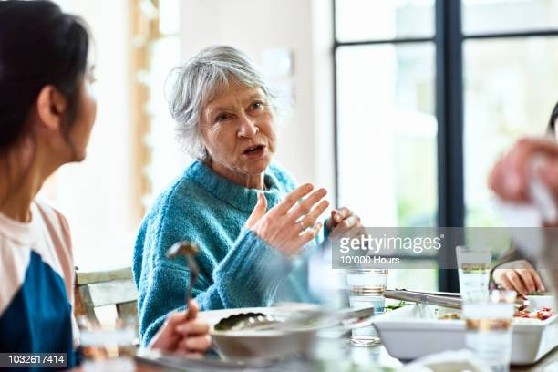 senior woman talking and gesturing at dinner party - storytelling stock pictures, royalty-free photos & images