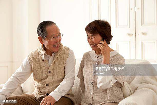 Senior woman talking on mobile phone next to her husband on sofa