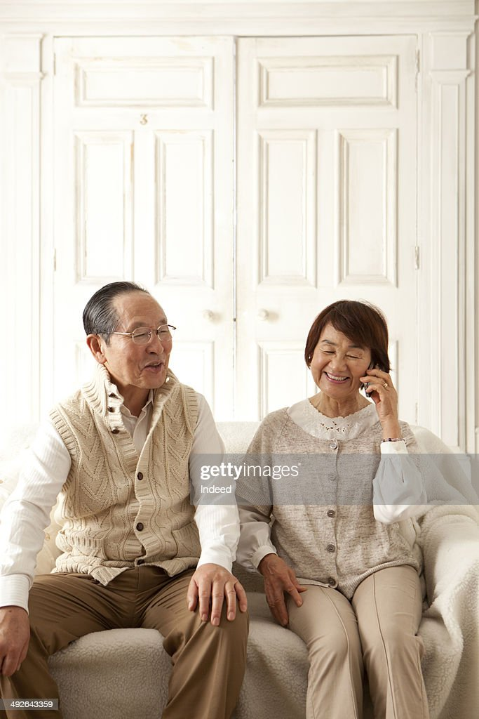 Senior woman talking on mobile phone next to her husband on sofa : Stock Photo