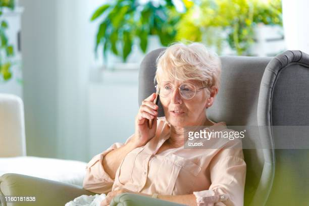 senior woman talking on mobile phone - ringing stock pictures, royalty-free photos & images