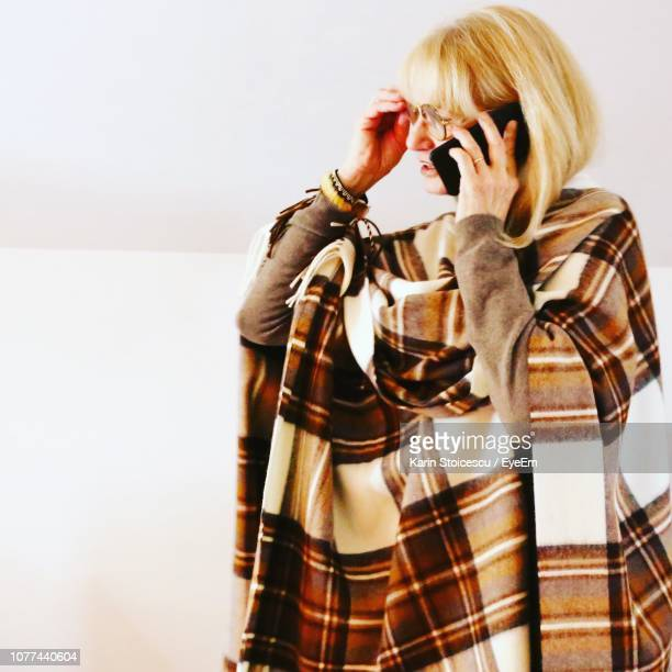 Senior Woman Talking On Smart Phone By Wall At Home