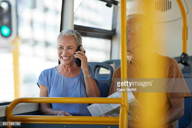 Senior woman talking on smartphone, while riding public bus