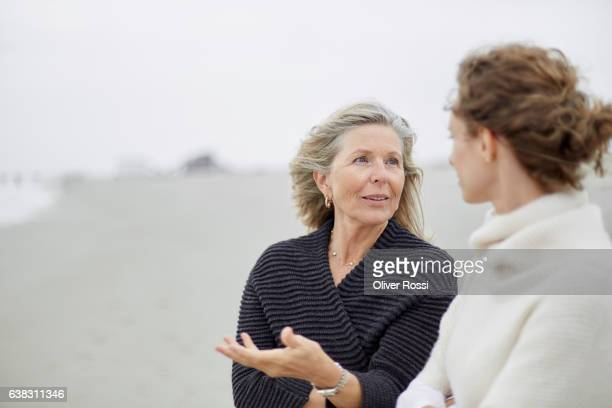 senior woman talking to adult daughter on the beach - two parents ストックフォトと画像