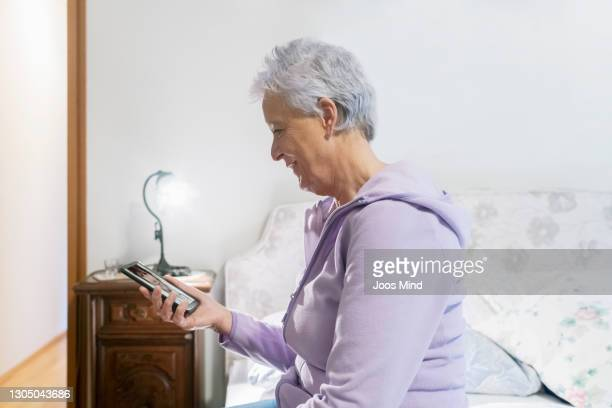 senior woman talking to female doctor on video call in bedroom using smart phone - mindzoom 2 stock pictures, royalty-free photos & images