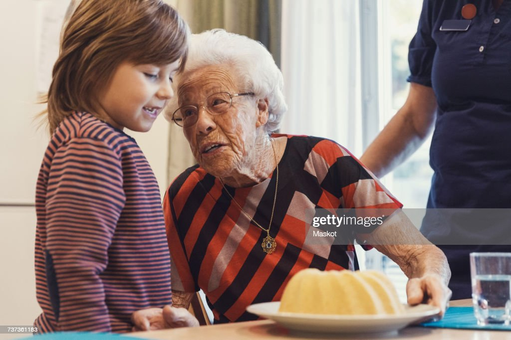 Senior woman talking to great grandson looking at sponge cake on table with caretaker standing at home : Stock Photo