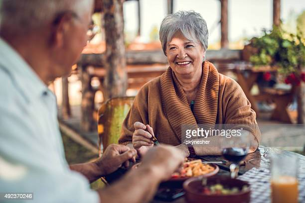 senior woman talking to her husband during a lunch. - senior lunch stock photos and pictures