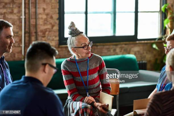 senior woman talking to small group in office training session - learning stock pictures, royalty-free photos & images