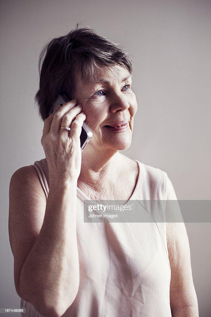 Senior woman talking via phone : Stock Photo