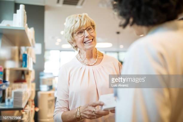 senior woman talking with chemist in drugstore - klanten georiënteerd stockfoto's en -beelden