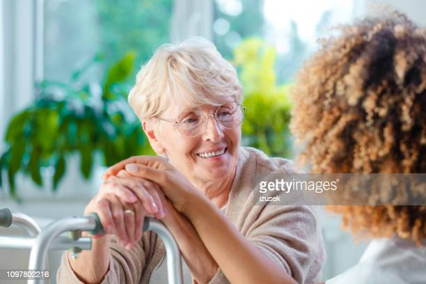 senior woman talking with female home caregiver - mental health stock photos and pictures