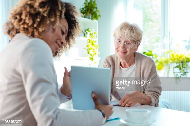 senior woman talking with financial advisor - nutritionist stock pictures, royalty-free photos & images