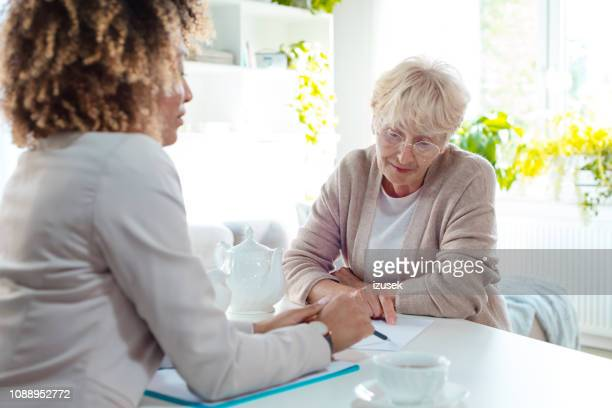 senior woman talking with insurance advisor - nutritionist stock pictures, royalty-free photos & images