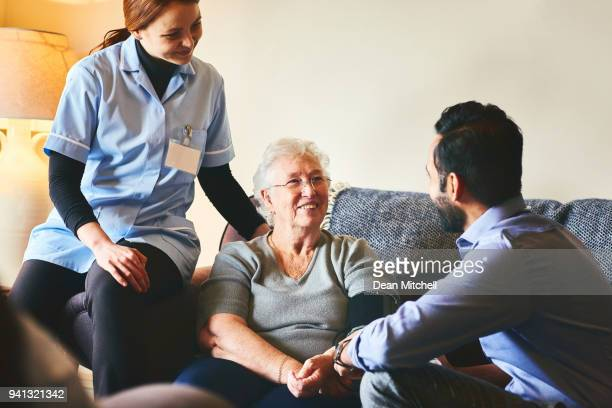 senior woman talking with young medics - house call stock pictures, royalty-free photos & images