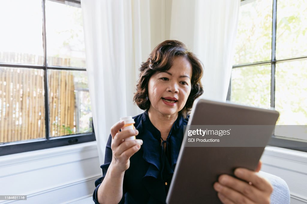 Senior woman talks with a doctor online : Stock Photo