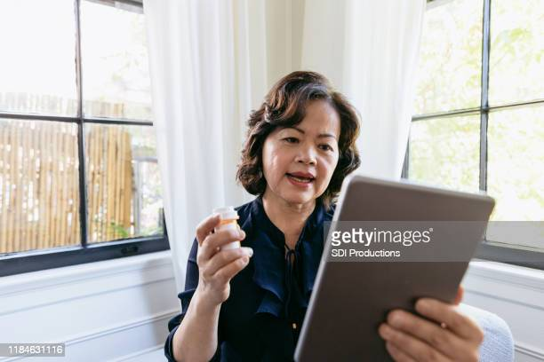 senior woman talks with a doctor online - telemedicine stock photos and pictures