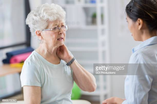 senior woman talks with doctor about neck pain - neck stock pictures, royalty-free photos & images