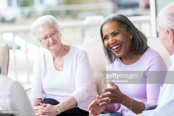 Senior woman talks with friends on front porch