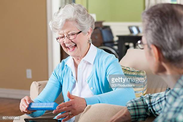 Senior woman talks with husband while holding a pill organizer