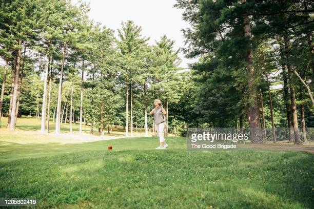 senior woman teeing off on golf course - wide shot stock pictures, royalty-free photos & images