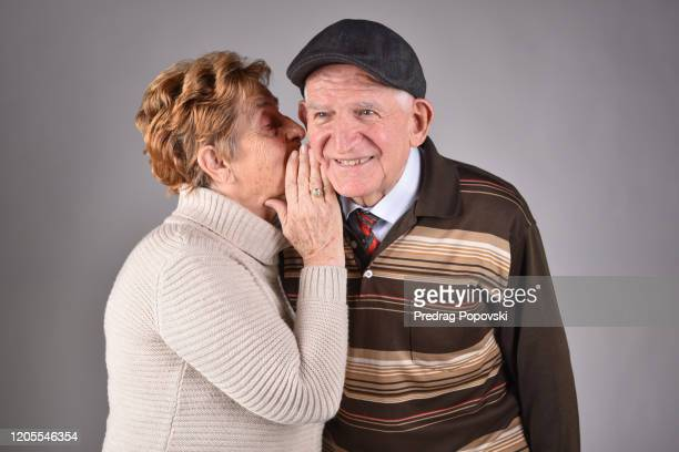 senior woman telling his husband secret studio portrait - gossip stock pictures, royalty-free photos & images