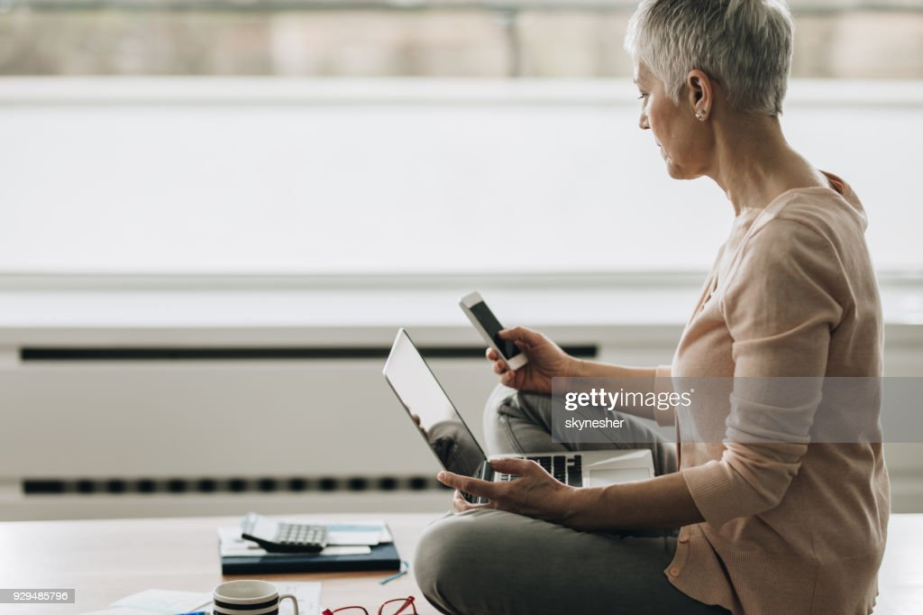 Senior woman text messaging on mobile phone while using computer at home. : Stock Photo