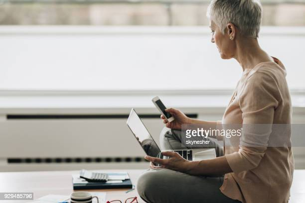senior woman text messaging on mobile phone while using computer at home. - candid forum stock pictures, royalty-free photos & images