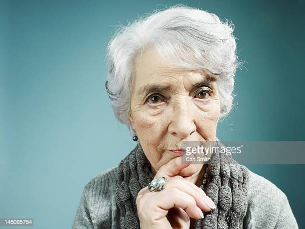 A senior woman thinking with her index finger to her lips