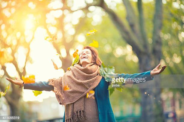 Senior Woman Throwing Maple Leaves