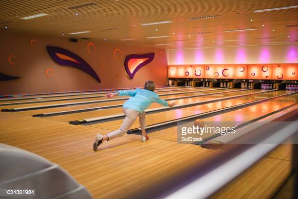 senior woman throwing the ball down the bowling alley - bowling alley stock pictures, royalty-free photos & images