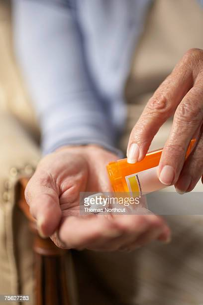 Senior woman tipping pills from prescription bottle, close-up of hands