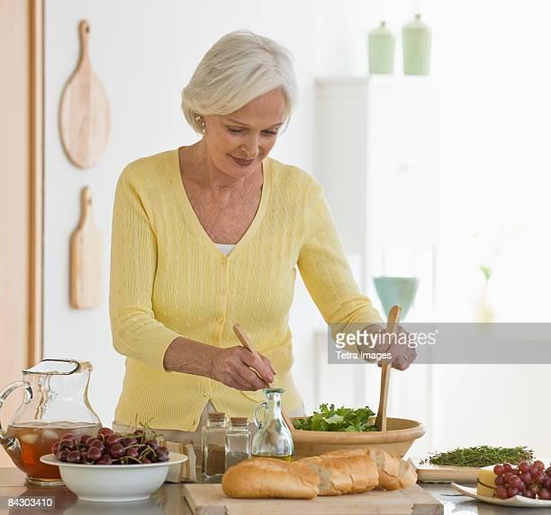 Senior woman tossing salad